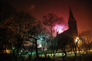 Pyhäinpäivän pamaus valaisee kirkon ympäristöä.