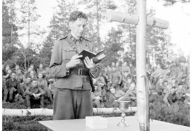 Sotilaspappi kenttäjumalanpalvelusta pitämässä sota-aikana (v.1940-44). Kuva: Uuno Laukka/Pohjois-Pohjanmaan museo