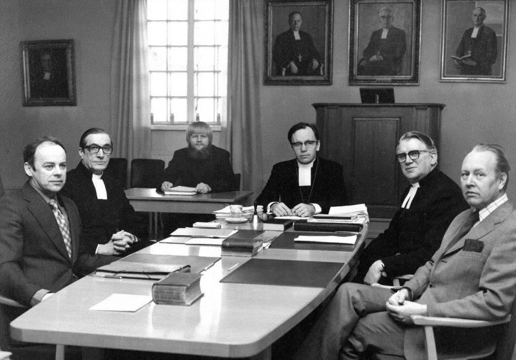 Porvoon hiippakunnan tuomiokapituliin kuuluivat joulukuussa 1975 (vasemmalta) jumaluusoppinut asessori Erik Wentin, tuomiorovasti Erik Paetau, notaari Gunnar Grönblom, piispa John Vikström, jumaluusoppinut asessori Thure Eriksson ja lainoppinut asessori Gunnar Träskman. Kuva: Porvoon tuomiokapituli.